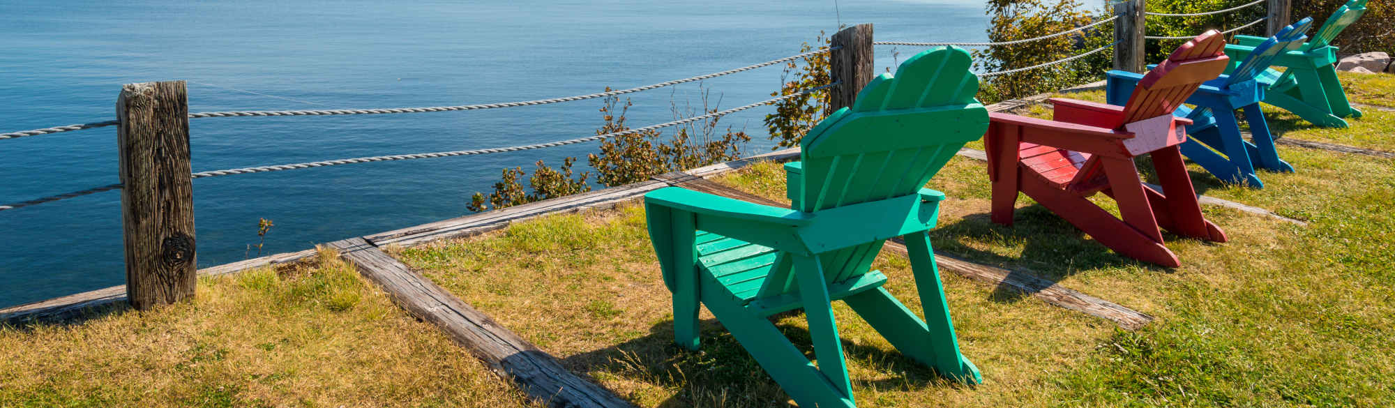 Colourful lawn chairs looking over water